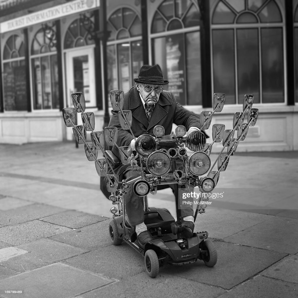 CONTENT] An elderly man rides along on a mobility scooter. The mobility scooter has been made to look like a mods scooter with mirrors and spotlights.He looks like an elderly mod.
