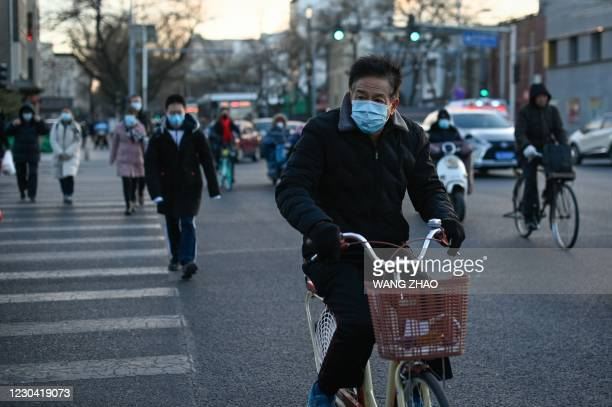 An elderly man riding his bicycle crosses a street in Beijing on January 4, 2021.