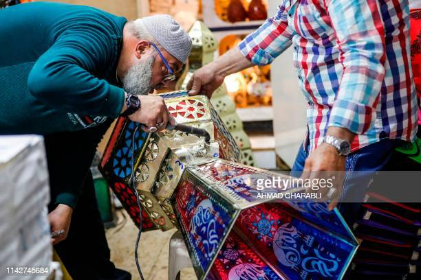An elderly man seals the parts of a lantern as Palestinian craftsman Issam Zughair holds it up in his shop in the old city of Jerusalem on May 2 2019...