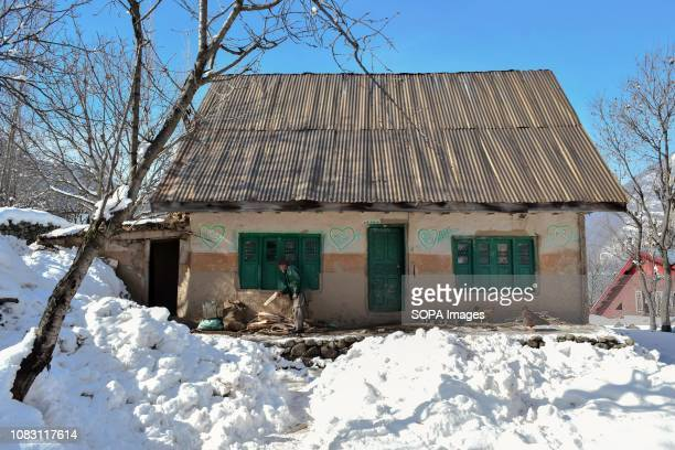 An elderly man seen assembling wooden pieces outside his house during a sunny winter day in Ganderbal about 50kms from Srinagar Indian administered...