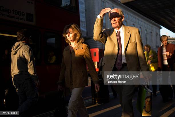 An elderly man shields his eyes from bright light while walking along Piccadilly in late afternoon sunshine Holding his hand across his eyes the man...
