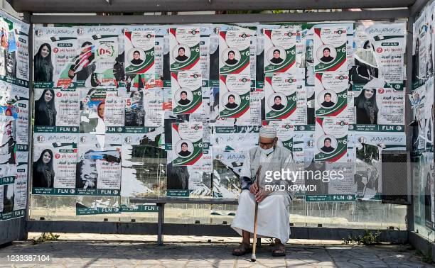 """An elderly man sits in a bus station covered with electoral posters of a candidate of the """"Future Front"""" political party in Algeria's capital Algiers..."""