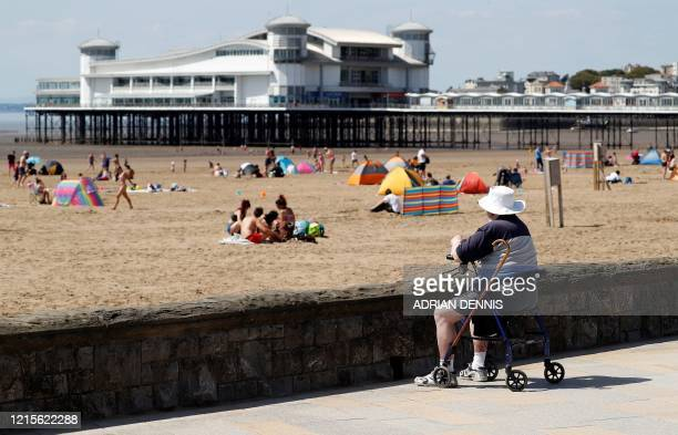 An elderly man sits on a walking aid as sunbathers enjoy the warm weather at the beach in Weston-super-Mare, south west England on May 27 after...