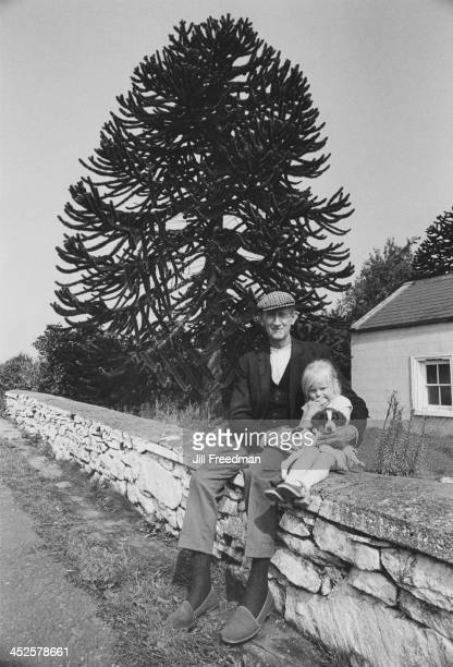An elderly man sits with his granddaughter on a country road Ireland 1974
