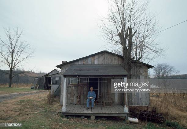 An elderly man sitting on the porch of his log house Pike County Kentucky US 1967
