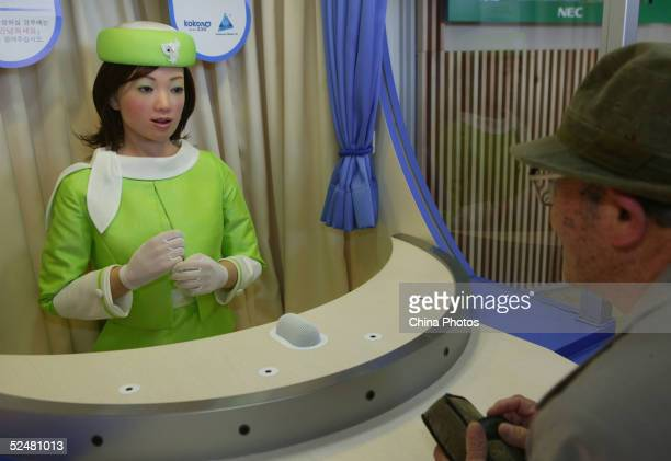 An elderly man speaks with Kokoro's robot 'Actroid' during the opening day of 2005 World Exposition Aichi on March 25 2005 in Nagakute town Aichi...