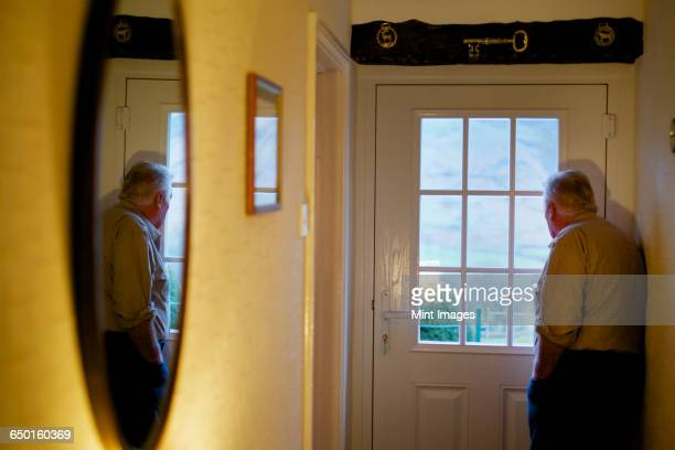 an elderly man standing by a door looking out through the window panes. - loneliness stock pictures, royalty-free photos & images