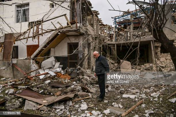 An elderly man stands in front of a destroyed house after shelling in the breakaway Nagorno-Karabakh region's main city of Stepanakert on October 7...