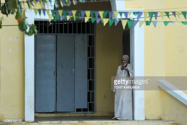 An elderly man stands in the doorway to a mosque next to a square lined with pennants close to the port at Moroni on July 27 2018 where an upcoming...