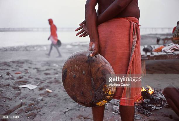 An elderly man stands near the mouth of the Ganges River where it meets the Yamuna river on October 29 2009 in Allahabad India Originating in Nepal...