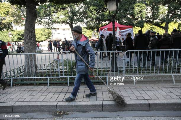 An elderly man sweeps up the trash on the street during the celebrations of the 9th anniversary of the revolution held on avenue Habib Bouguiba in...