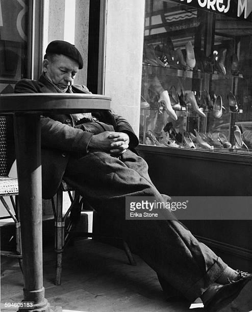 An elderly man takes a nap in a cafe next to a shoe shop in Paris France 1957