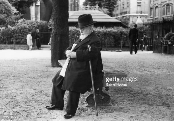 An elderly man takes a nap on a bench in the garden of Notre Dame cathedral Paris circa 1950