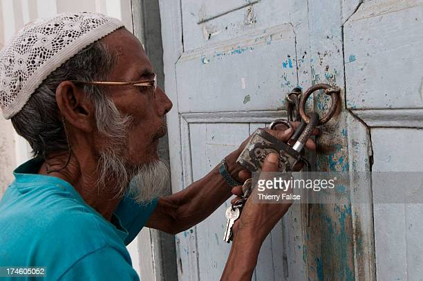 An elderly man trying to lock the door