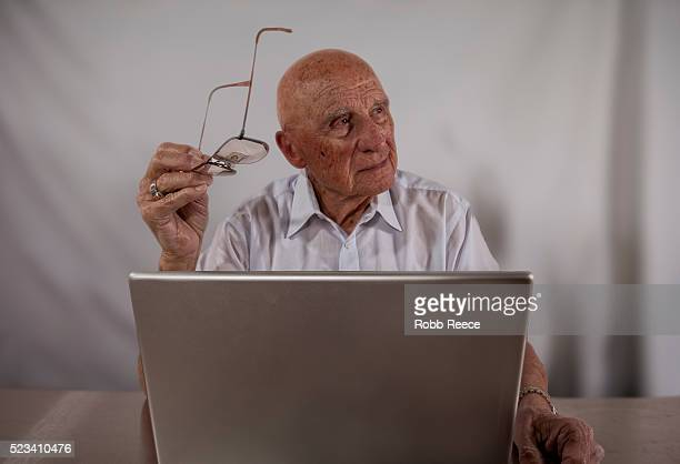 an elderly man using a laptop computer - robb reece stockfoto's en -beelden
