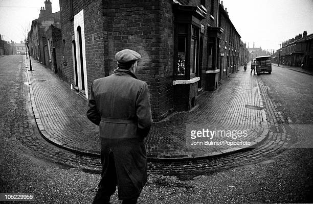An elderly man views a milkman delivering milk from a street corner in the Black Country, West Midlands, January 1961. The area was known for its...