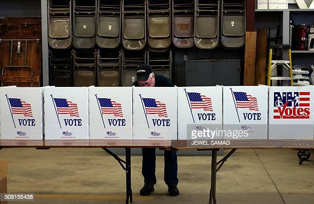 An elderly man votes for the first US presidential primary at a fire station in Loudon New Hampshire on February 9 2016 New Hampshire began voting on...