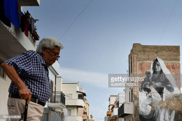 An elderly man walks accross a street in Lampedusa on September 25 2018 Five years after the worst shipwreck of its history the largest island of the...
