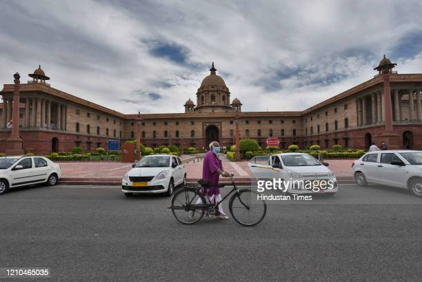 An elderly man walks along with his bicycle in the direction of the Prime Minister's office, at Raisina Hills on April 20, 2020 in New Delhi, India....