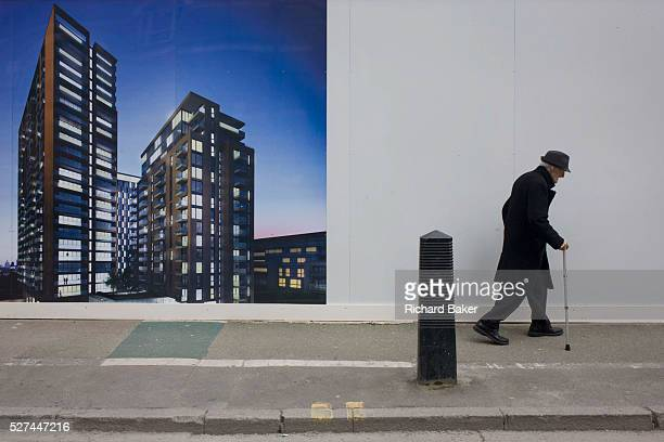 An elderly man walks bent past a regeneration project hoarding image at Elephant Castle London borough of Southwark The older generation sees their...