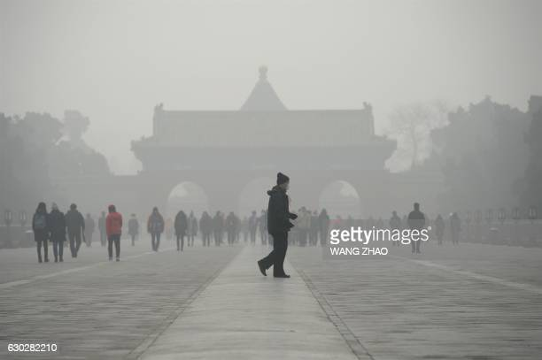 TOPSHOT An elderly man walks in front of a group of people during heavy smog at a the Temple of Heaven park in Beijing on December 20 2016 Heavy smog...