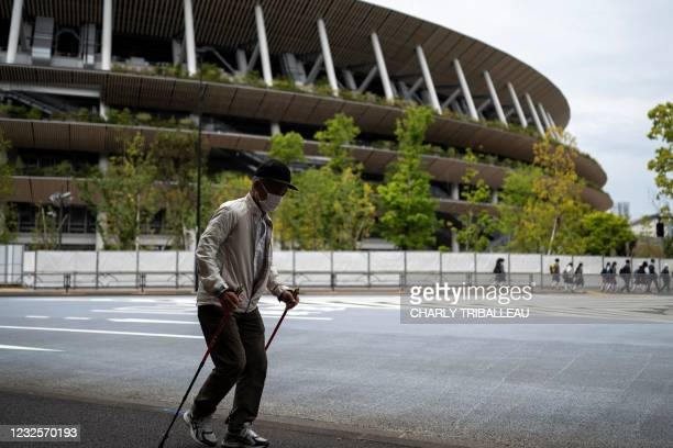 An elderly man walks near the National Stadium, main venue for the Tokyo 2020 Olympic and Paralympic Games in Tokyo on April 28, 2021.