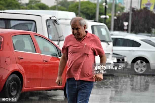An elderly man walks outside a shopping mall during heavy rainfall in the spring season in Ankara Turkey on Sunday May 20 2018
