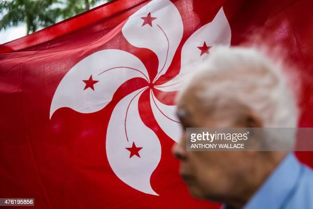 An elderly man walks past a Hong Kong flag displayed within an area set aside for proBeijing activists on the sidelines of a gathering in the Tsim...