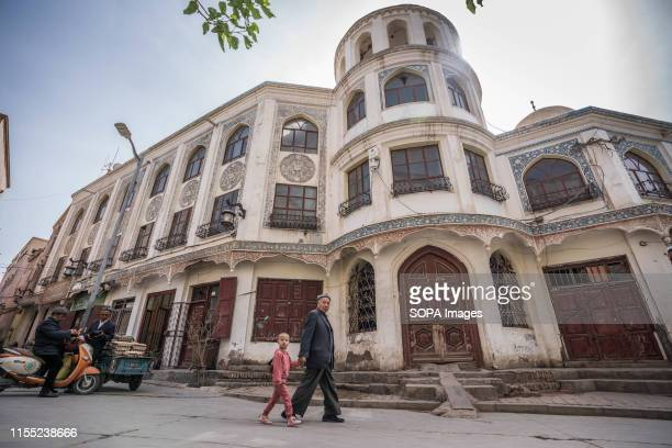 An elderly man walks with a child in front of a historic building the in old town of Kashgar. The Xinjiang province is located in the North Western...