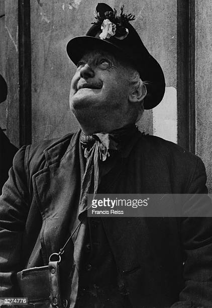 An elderly man watches the VE Day celebrations with flowers in his hat 8th May 1945 Original Publication Picture Post 1991 This Was VE Day In London...
