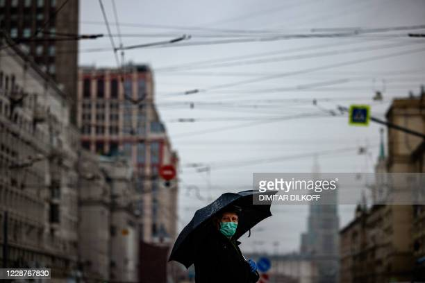 An elderly man wearing a face mask and gloves to protect against the coronavirus disease walks with an umbrella in Moscow on September 28, 2020.