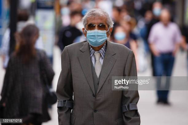 An elderly man wearing a face mask waits at a pedestrian crossing amid Saturday afternoon shoppers on Oxford Street in London, England, on June 20,...