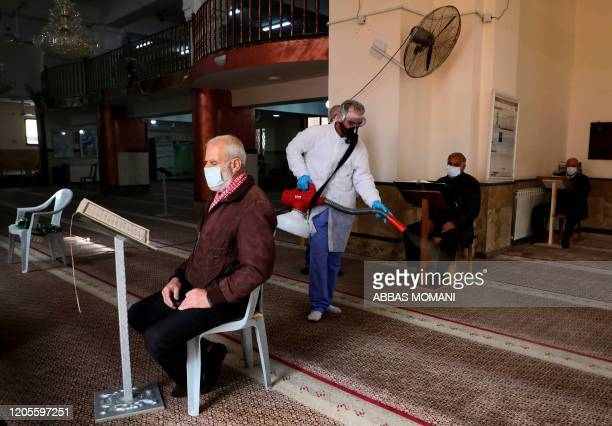 An elderly man wearing a health face mask reads from the Holy Koran while seated in a mosque being sterilised by Palestinian health workers in the...