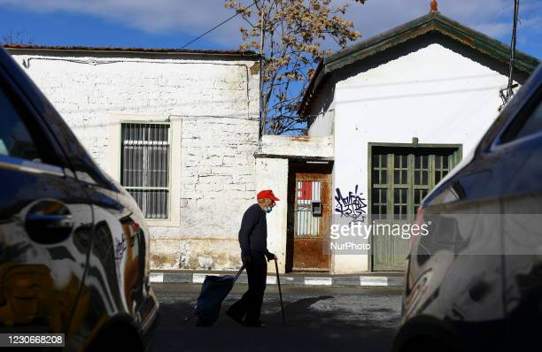 An elderly man wearing a protective mask carries groceries in a bag from a store in Limassol. Cyprus, Tuesday, January 19, 2021. Cyprus could default...