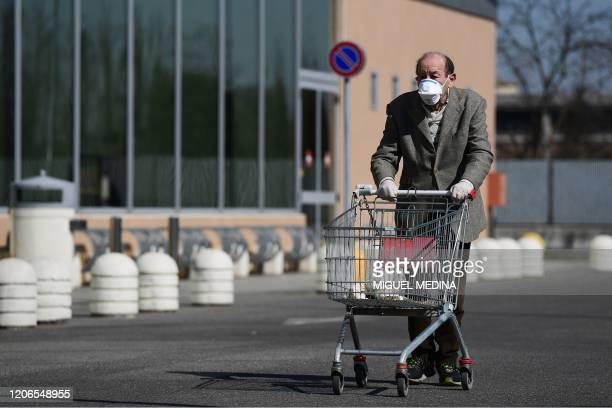 An elderly man wearing a protective mask pushes his cart as he arrives to shop at a supermarket in Codogno southeast of Milan on March 11 2020 a day...