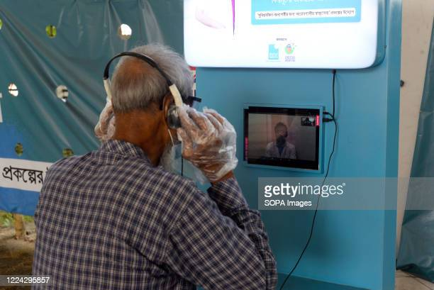 An elderly man wearing hand gloves is seen talking with a doctor through a video chat during the Covid-19 testing. Mugda Medical College and Hospital...