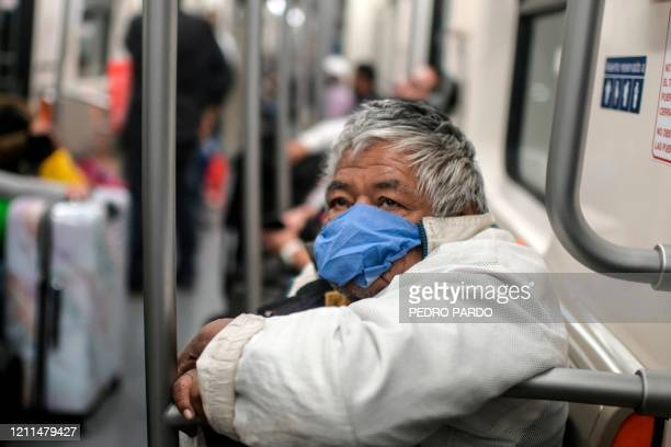 An elderly man wears a face mask as a preventive measure against the spread of the new coronavirus as he rides the subway in Mexico City, on May 1,...