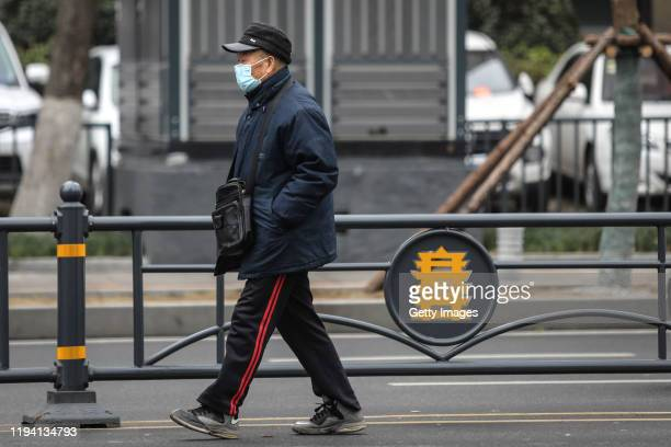 An elderly man wears a mask while walking past the closed Huanan Seafood Wholesale Market which has been linked to cases of Coronavirus on January 17...