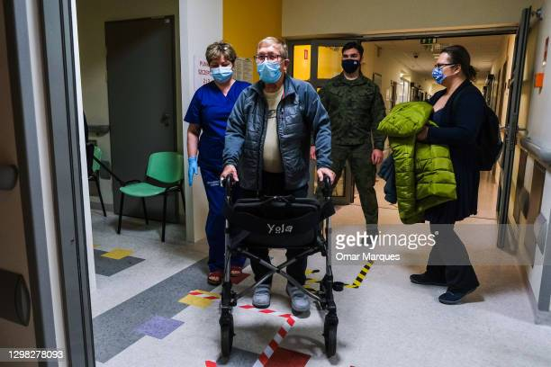 An elderly man wears a protective face mask and walks towards the observation room after being given a Pfizer/BioNTech COVID-19 jab at the Krakow...
