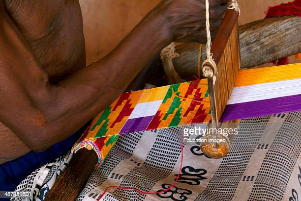 An elderly man weaves traditional kente cloth in the weaving craft village of Adanwomase in the Ashanti Region of Ghana West Africa Kente cloth is...