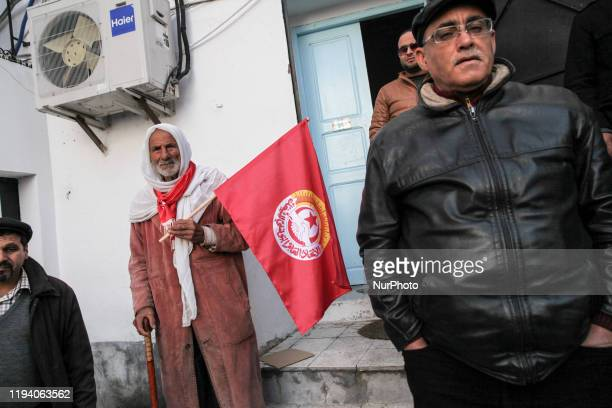 An elderly man with a crutch holds the flag of the UGTT labor union as he attends the gathering held outside the UGTT headquarters in Tunis to...