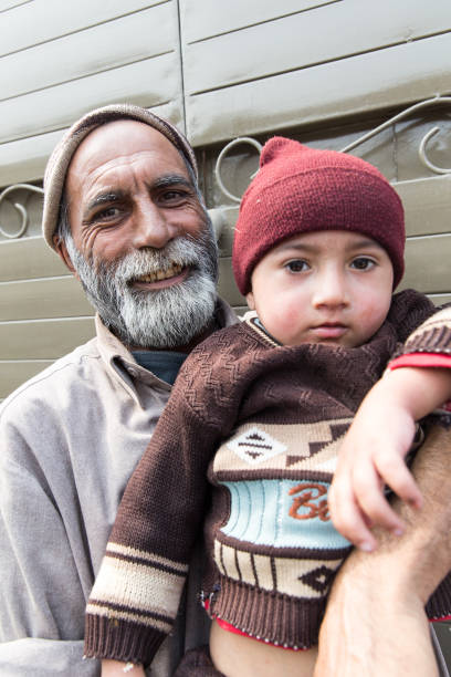 An elderly man with a grey beard is holding a young child in his arms on February 27 2014 in Lahore Pakistan Lahore is the capital city of the...