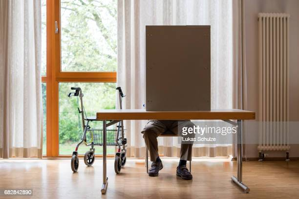 An elderly man with a rollator casts his ballot in state elections in North RhineWestphalia on May 14 2017 in Wuerselen Germany The election today...