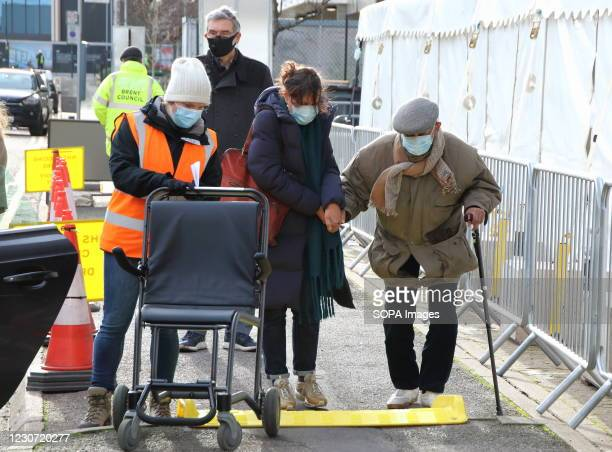 An elderly man with a walking stick is being helped into the vaccination centre by a carer. A steady stream of elderly people with pre-booked...