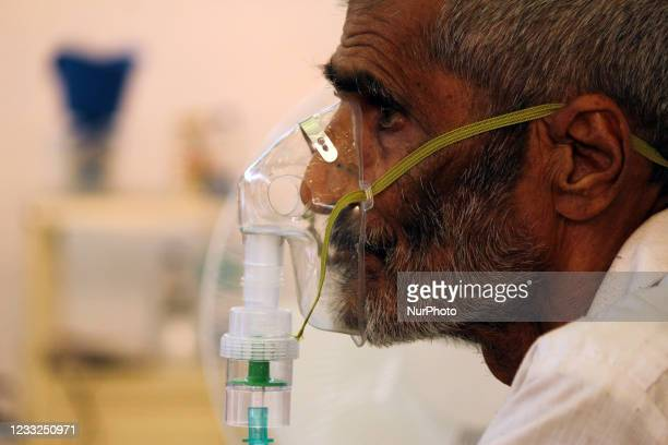 An elderly man with breathing difficulty due to coronavirus takes oxygen with the help of an oxygen mask at a COVID-19 care facility, inside...