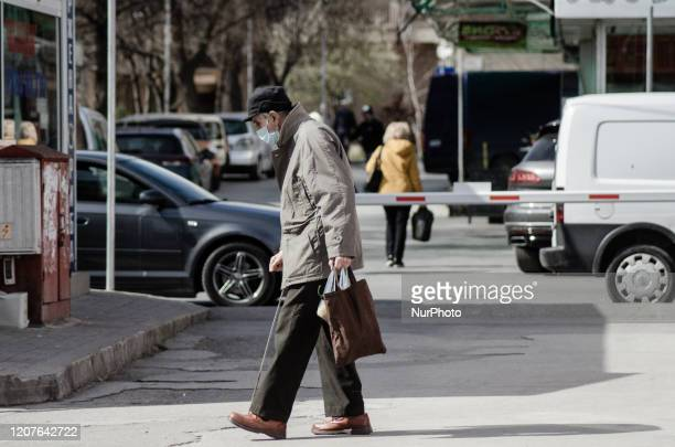 An elderly man with protective mask is seen walking in Varna, Bulgaria, on March 18, 2020. The Bulgarian government banned people from gathering in...
