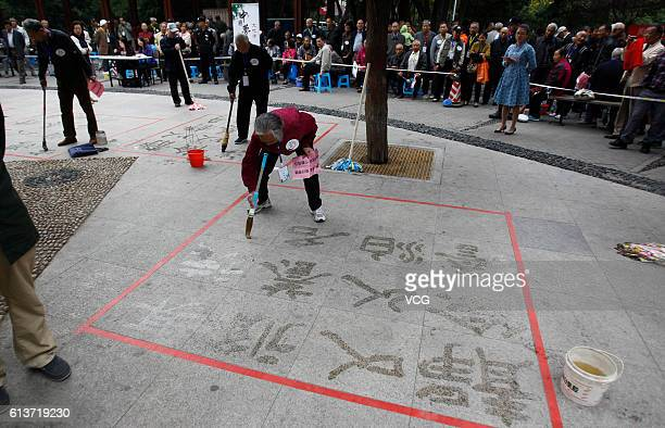 An elderly man writes Chinese characters with Chinese brushes for calligraphy on the ground during a handwriting competition at Henan Worker Cultural...