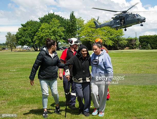 An elderly Maori woman is accompanied by a family members after she was evacuated by air force helicopter from Kaikoura to Christchurch on November...