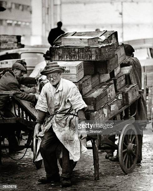 An elderly market porter pulling a barrow loaded with boxes at Billingsgate fish market London 1961