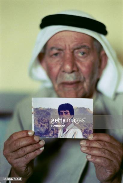 An elderly Middle Eastern man, wearing a white keffiyeh with a black band, holding a photograph of a young Middle Eastern man man, in an unspecified...